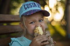 Het meisje op de bank eet straatvoedsel stock afbeelding