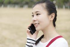 Het meisje is op de telefoon Stock Foto