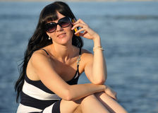 Het meisje op de telefoon dichtbij de rivier Stock Foto's