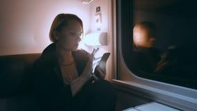 Het meisje is op de trein bij nacht Zit op de trein en gebruikt een smartphone stock videobeelden