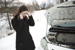 Het meisje op de de winterweg roept de telefoon dichtbij de auto Royalty-vrije Stock Foto's