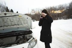 Het meisje op de de winterweg roept de telefoon dichtbij de auto Royalty-vrije Stock Afbeelding