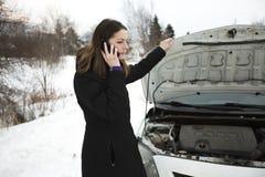 Het meisje op de de winterweg roept de telefoon dichtbij de auto Royalty-vrije Stock Afbeeldingen