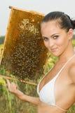 Het meisje op een bijenstal stock afbeeldingen