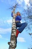 Het meisje op een boom Stock Foto