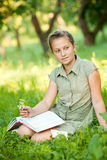 Het meisje op een gras met boek Royalty-vrije Stock Foto