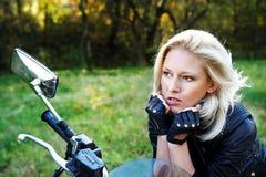 Het meisje op een motorfiets stock foto