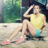 Het meisje op een skateboard Stock Afbeeldingen