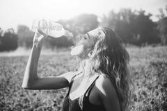 Het meisje op gebied van papaverzaad drinkt water van fles royalty-vrije stock foto's