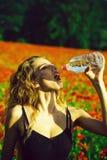 Het meisje op gebied van papaverzaad drinkt water van fles stock fotografie