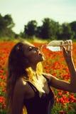 Het meisje op gebied van papaverzaad drinkt water van fles stock afbeeldingen