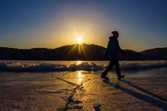 Het meisje is op het ijs van Meer Baikal in het licht van plaatsende su Stock Foto's