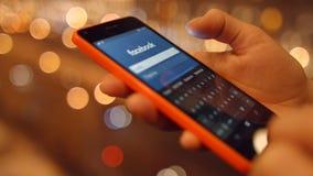 Het meisje op mobiele telefoon komt in sociale netwerken Facebook 4K 30fps ProRes stock videobeelden