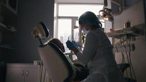 Het meisje op ontvangst bij de tandarts, stomatologist onderzoekt de kind` s tanden stock footage