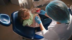 Het meisje op ontvangst bij de tandarts, stomatologist onderzoekt de kind` s tanden, het leuke en ongehoorzame meisje glimlachen stock video