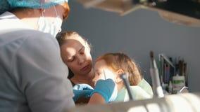 Het meisje op ontvangst bij de tandarts, stomatologist onderzoekt de kind` s tanden, het ongehoorzame meisje glimlachen stock videobeelden