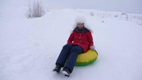 Het meisje op sneeuwplaat rolt neer van hoge sneeuwberg en lacht met genoegen Tienerspelen in de winter met sleeën stock video