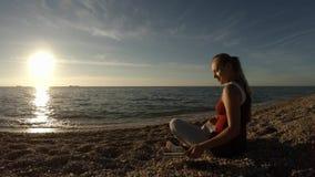 Het meisje op het strand neemt een beeld van de zonsondergang op het strand stock videobeelden