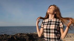 Het meisje op strand schommelt en stenenoverzees stock video