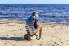 het meisje op het strand, tegen de achtergrond van stenen, zand en mooie golven van het overzees en het lawaai van de wind, zit a royalty-vrije stock foto