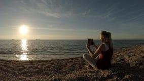 Het meisje op het strand zit met een tablet stock video
