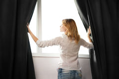 Het meisje opent de gordijnen en het ontspannen in ochtend royalty-vrije stock foto