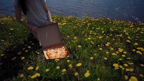Het meisje opent kartondoos met pizza op zeekust stock video