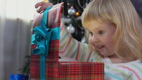 Het meisje opent nieuwe jaar` s gift stock videobeelden