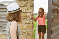 Het meisje opent voordeur, meisjes, omhelzingen op de vergadering worden begroet die royalty-vrije stock afbeelding