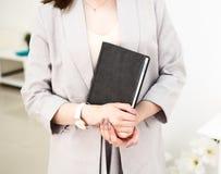 Het meisje overhandigt een boek in haar handen, gekleed in grijs jasje Zij heeft een polshorloge op haar hand Witte achtergrond royalty-vrije stock foto