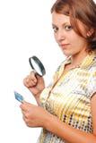 Het meisje overweegt een creditcard door meer magnifier stock foto