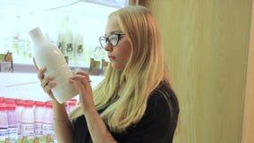 Het meisje overweegt een fles melk in de supermarkt stock footage