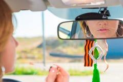 Het meisje past lippenstift achter het wiel van de auto toe Royalty-vrije Stock Afbeelding
