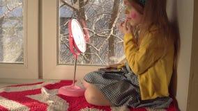 Het meisje past make-up voor Carnaval op haar gezicht toe stock videobeelden