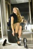 Het meisje past op laarzen in een boutique Stock Afbeeldingen