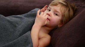 Het meisje port haar vinger in haar neus Peinzend kind stock footage
