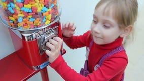 Het meisje port muntstuk in machineverkoop van snoepjes stock footage