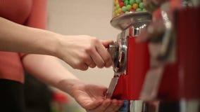 Het meisje port muntstuk in machineverkoop van snoepjes stock video