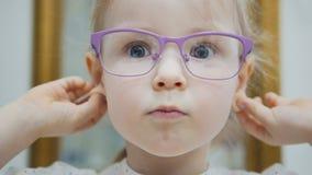 Het meisje probeert manier medische glazen dichtbij spiegel - winkelend in oftalmologiekliniek stock afbeeldingen