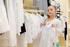 Het meisje probeert op blouse in kledingsopslag Stock Afbeelding