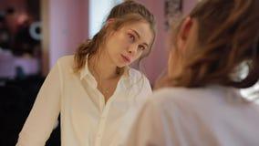 Het meisje probeert op oorringen in de schoonheidssalon stock footage