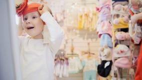 Het meisje probeert op oranje baret voor de spiegel Royalty-vrije Stock Afbeeldingen
