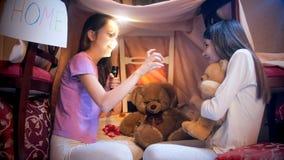 Het meisje in pyjama's doet schrikken haar vriend met griezelig verhaal bij nacht royalty-vrije stock foto