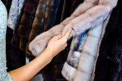 Het meisje raakt het bont op de bontjas Het kiezen van een bontjas in de opslag stock fotografie