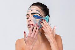 Het meisje raakt de samenstelling met de vingers van beide handen op een grijze achtergrond Royalty-vrije Stock Foto's