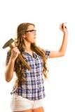 Het meisje raakt de spijker met een hamer Stock Fotografie