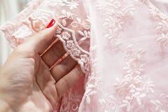 Het meisje raakt het gevoelige roze kant stock fotografie