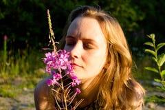 Het meisje raakt zacht haar neus aan de bloem en inhaleert zijn gevoelige geur Voor een de zomer zonnige dag, de stralendaling op Stock Foto's
