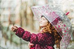Het meisje rekt haar hand uit om dalende regendruppel te vangen Stock Foto's
