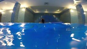 Het meisje rent ongeveer in het zwembad weg stock video